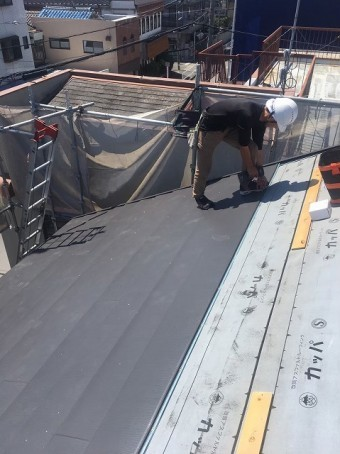 職人が屋根材を貼る様子